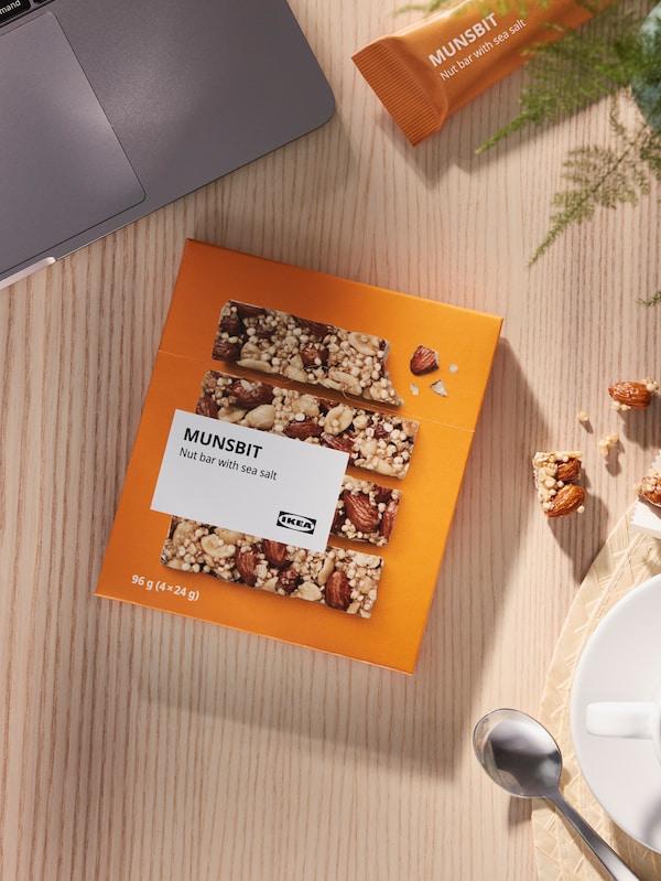En oransje pakke med MUNSBIT nøttebar på et trebord ved siden av en kaffekopp og en laptop.