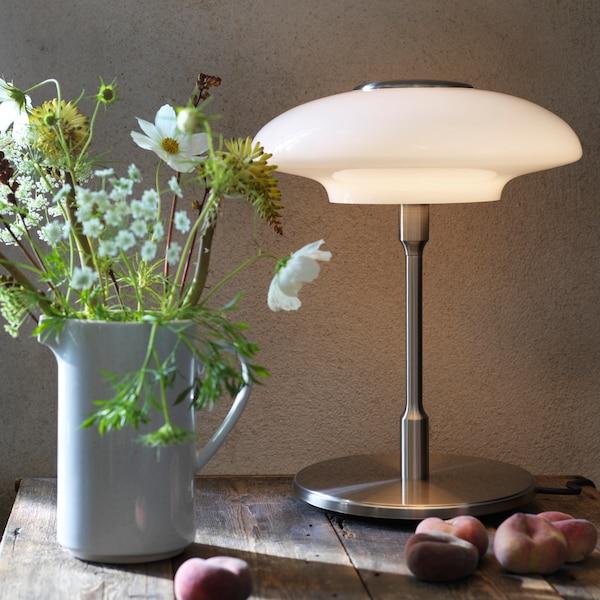 На белой комбинации для хранения стоит лампа с абажуром из серого дымчатого стекла и медным основанием. Рядом стопка книг, на ней стоит декоративная шкатулка.