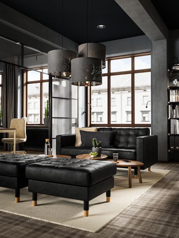 Ett mörkt rum med högt i tak och stort fönsterparti är möblerat med LANDSKRONA soffa och fotpallar i svart skinn ståendes på en ljus matta.