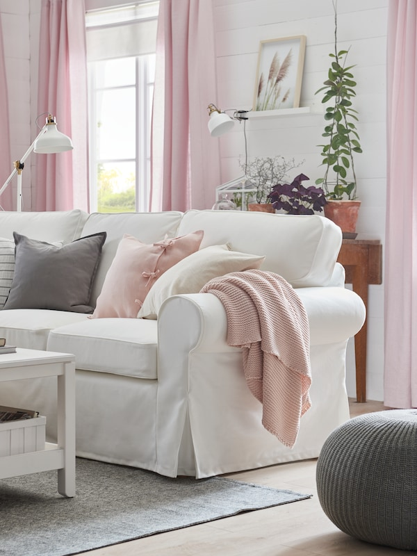 Light-pink LENDA curtains opened to allow light into a living room with SANDARED pouffe and white EKTORP sofa.