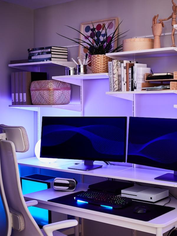 パソコンモニター2台、本、デコレーションアイテム、ブルーの光のランプが置いてあるシェルフユニット。その前にはオフィスチェアがある。