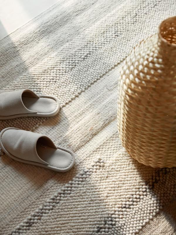 Des chaussons de couleur crème et un vase en bambou tressé sont posés sur un tapis BRÖNDEN tissé à la main.