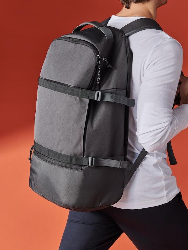 Un homme qui marche portant un sac à dos VÄRLDENS gris foncé sur son dos, sur fond orange.
