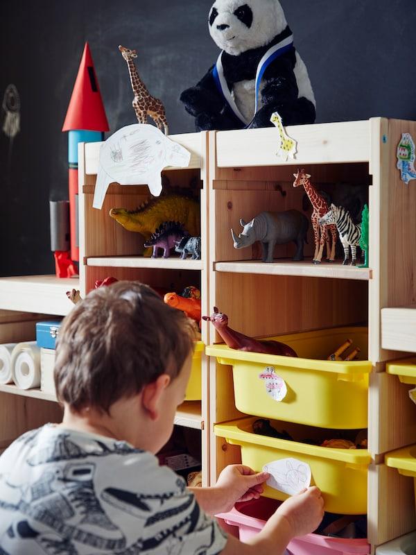 Un neno pon unha etiqueta nunha caixa dunha unidade de almacenaxe TROFAST de piñeiro branco tinguido con estantes e caixas de cores ateigadas de xoguetes.