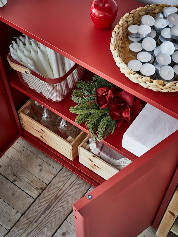Armario IVAR rojo con una cesta con velas en la parte superior y otra cesta, cajas, decoración navideña y servilletas dentro.