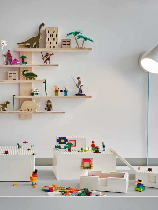 Cărămizile și cutiile BYGGLEK LEGO® stau pe o masă de activitate DUNDRA. O veioză și o poliță de perete LUSTIGT sunt pe peretele din spate.