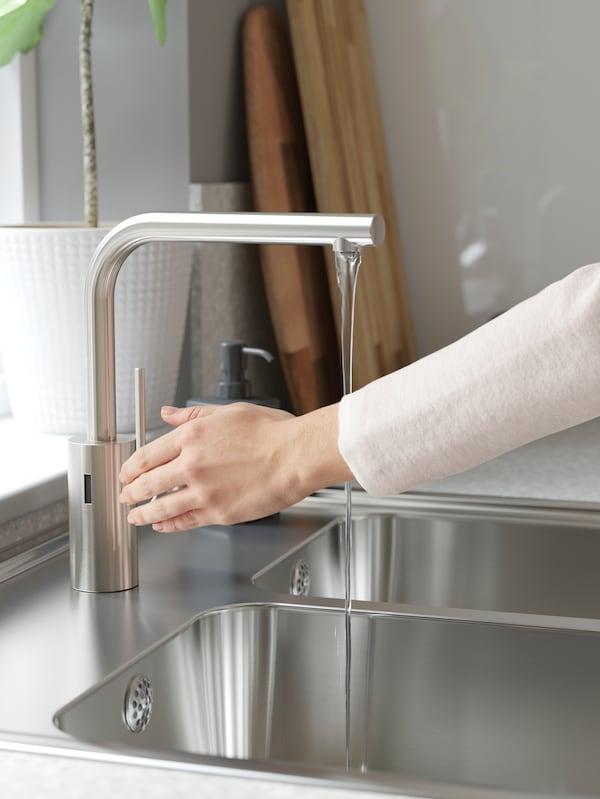 En kvinde rækker hånden ind foran sensoren på INSJÖN blandingsbatteri