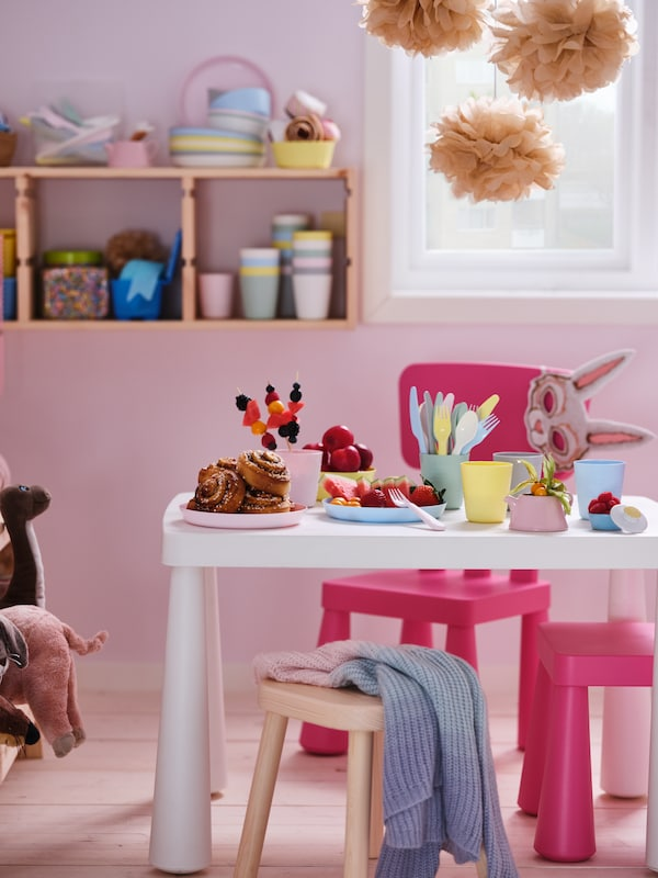 A pastel room with pink MAMMUT children's chairs around a white MAMMUT children's table set with colourful snacks.
