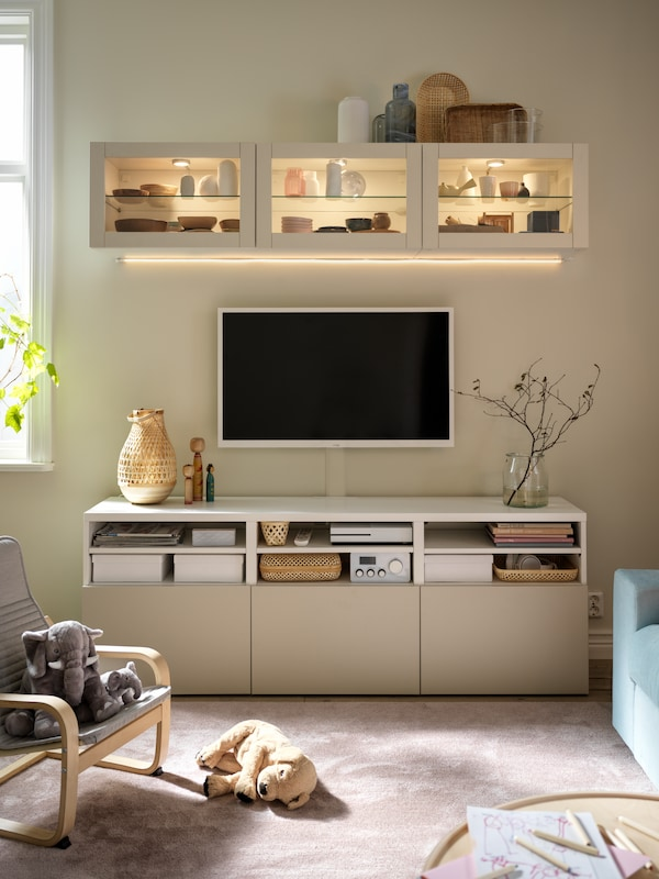 A wall-mounted TV and white BESTÅ cabinets, with glass doors above and light-grey/beige doors below.