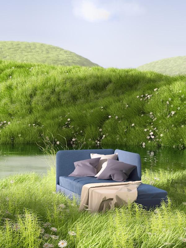 Mellomblå BLÅKULLEN sengestamme med hodegavl i hjørnet, pledd og puter ved en dam i ei frodig blomstereng.