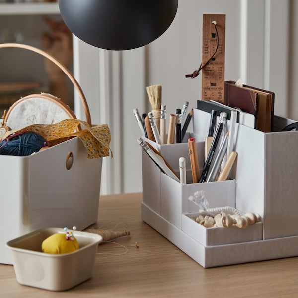 Close up of a white desk organizer, used to store pencils, paintbrushes, a notebook, and other bric-a-brac.