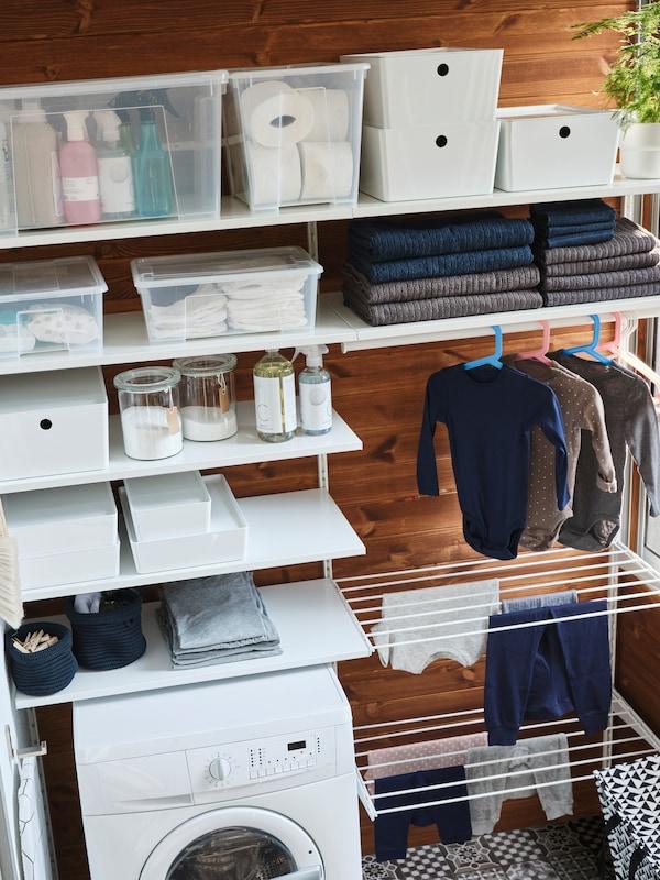 Ein weisses BOAXEL Aufbewahrungssystem mit vielen Böden, zwei Wäschetrocknern und einer Kleiderstange für längere Kleidungsstücke