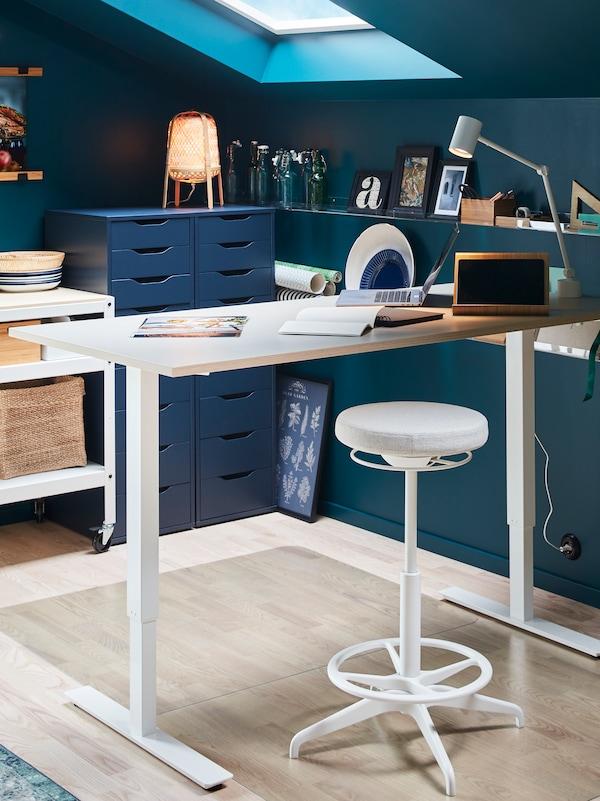 LIDKULLEN-istumis-/seisomistuki korkeussäädettävän työpöydän vieressä. Läpinäkyvät lattiansuojukset suojaavat lattiaa naarmuilta.