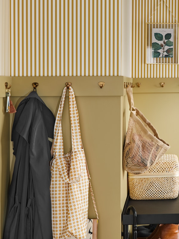 KVASP hooks on a beige wall with striped wallpaper, holding keys, clothes and bags. Below is a black table with a basket.