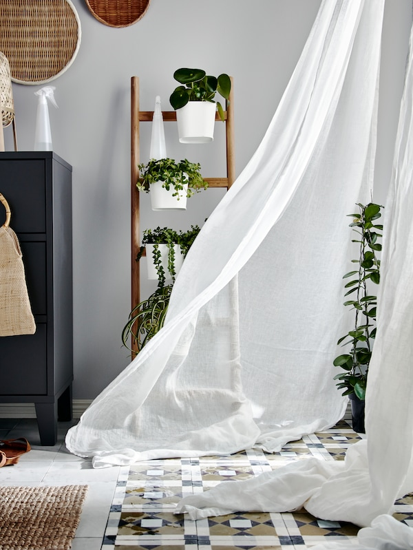 A white curtain is blown into a bedroom by the wind. Behind the curtain is a SATSUMAS plant stand with plants on it.