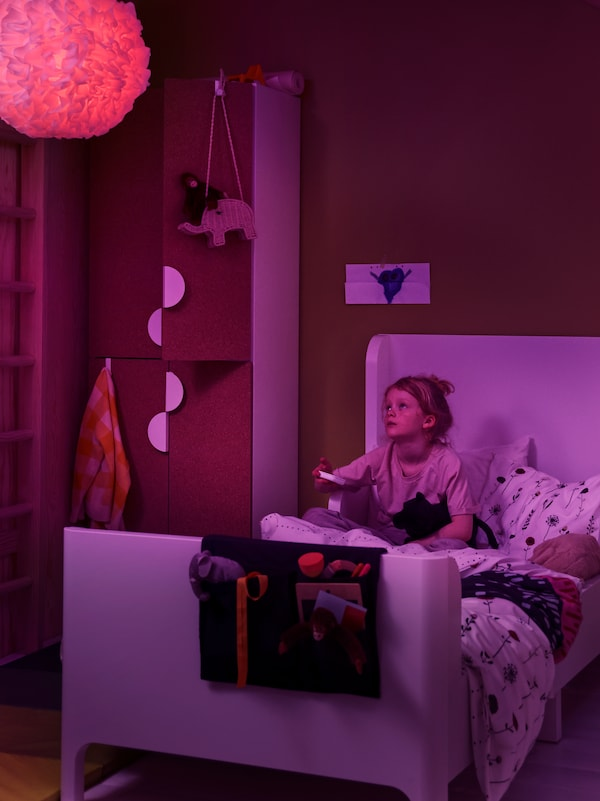 A girl uses a STYRBAR remote control to change the colour of a TRÅDFRI LED bulb to purple in a VINDKAST pendant lamp.