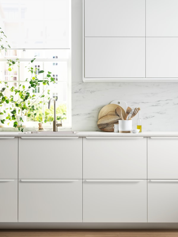 A sleek kitchen with wall-mounted and base cabinets with white fronts, a sink and a white marble-effect wall panel.