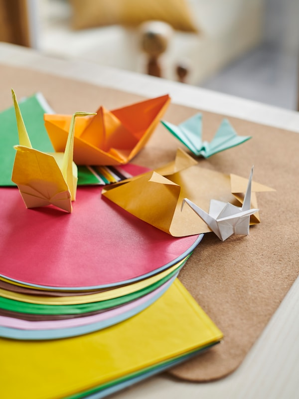 A table top holding multicolored LUSTIGT origami paper in different shapes, as well as some completed origami objects.