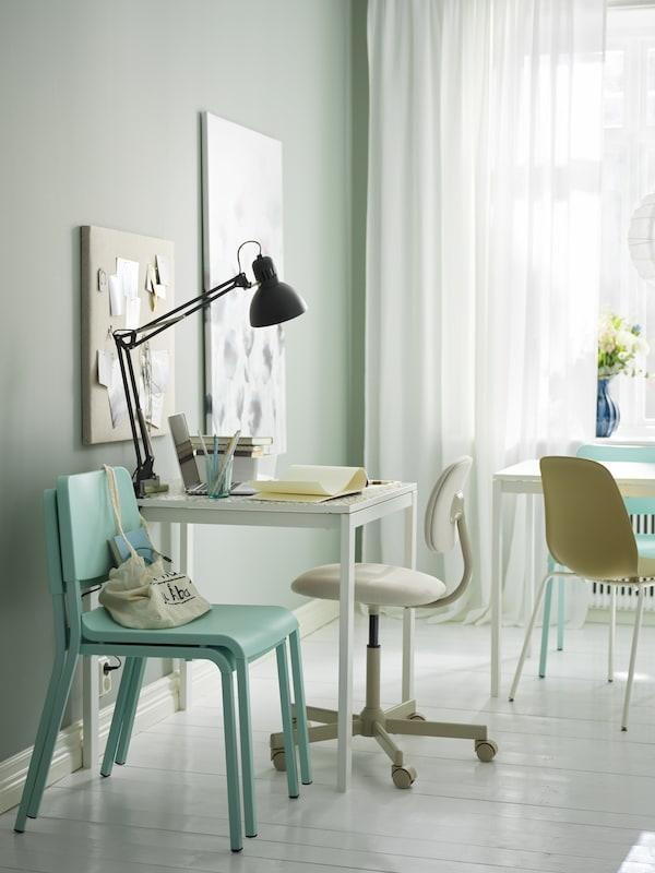 Vaaleassa huoneessa on valkoinen MELLTORP-pöytä ja BLECKBERGET-työtuol sekä vaalenavihreitä TEODORES-tuoleja pinossa.