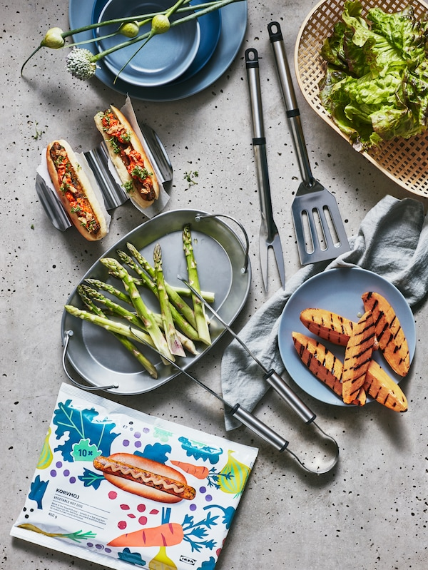 Rozstawione na stole naczynia z grillowanymi szparagami i batatami oraz warzywnymi hot dogami KORVMOJ z dodatkami. Pomiędzy nimi leżą przybory do grillowania z serii GRILLTIDER BBQ.