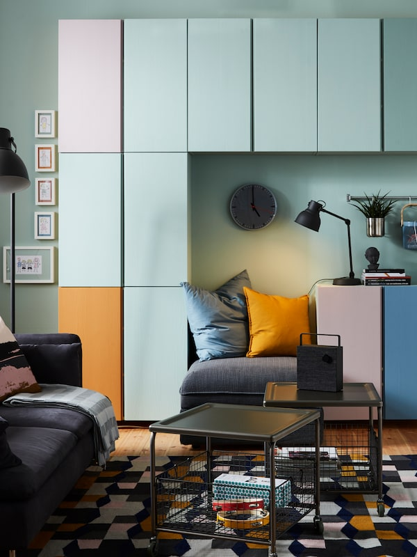 A living room area with multi-coloured IVAR storage units on the wall.