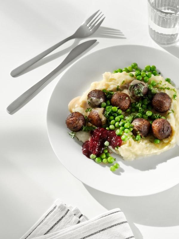 Eine Mahlzeit aus HUVUDROLL Proteinbällchen mit Erbsen und Kartoffelpüree auf einem Teller, daneben sind eine Serviette, Besteck und ein Glas Wasser zu sehen.