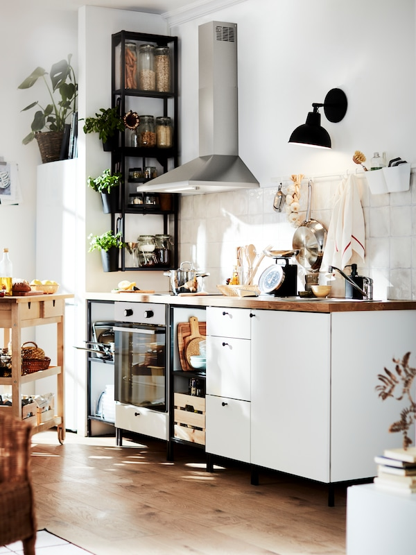 An ENHET kitchen with white fronts and black open shelves, a thick wooden worktop, a black wall lamp, a wooden trolley.