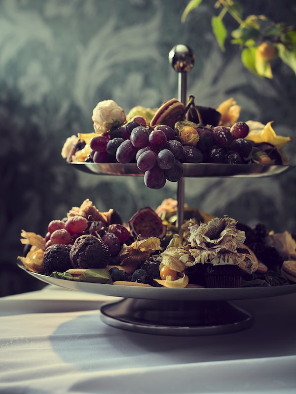 An INBJUDEN serving stand with a lavish display of fruits, berries and snacks, set on a table against a floral-pattern wall.