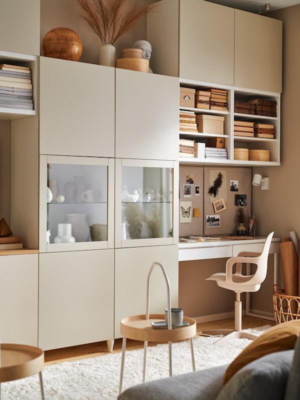 Estante BESTA bege a preencher toda uma parede, no canto mais à direita a estante não tem portas e está cheia de livros sob uma secretária, junto a uma cadeira.