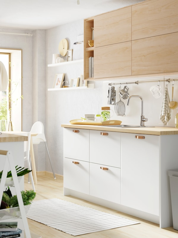 A light-filled white kitchen in a mix of white and wood with a TUTEMO open cabinet and a white highchair.