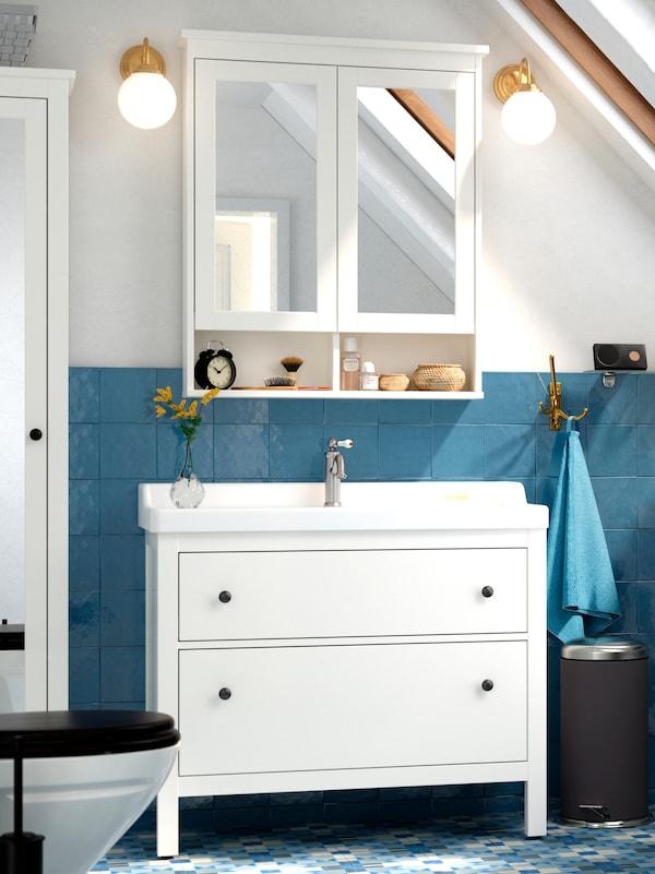 В бело-серой ванной белый шкаф под раковину с двумя выдвижными ящиками, белый зеркальный шкаф с двумя дверцами и картины на стенах.