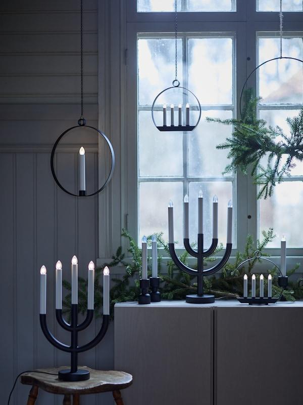 Musta STRÅLA 5-haarainen LED-kynttilä on puisella jakkaralla ikkunan edessä.