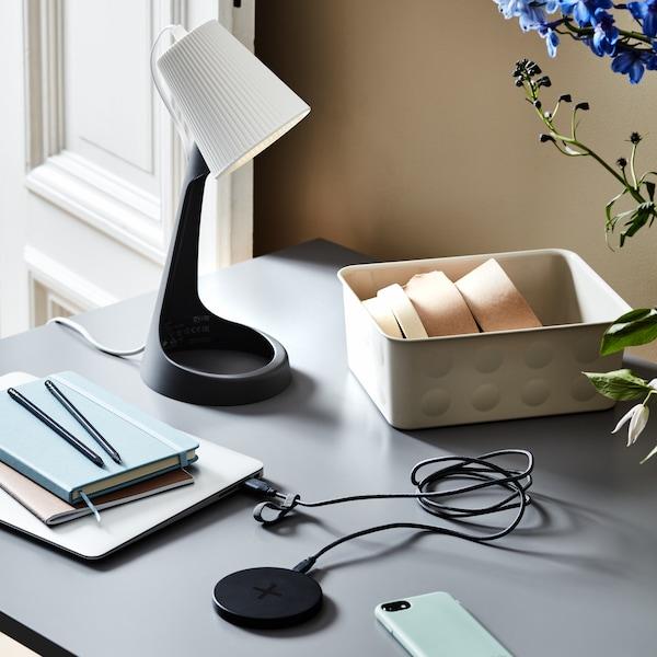 Un primo piano di una scrivania con lampada da tavolo SVALLET e pad di ricarica LIVBOJ.