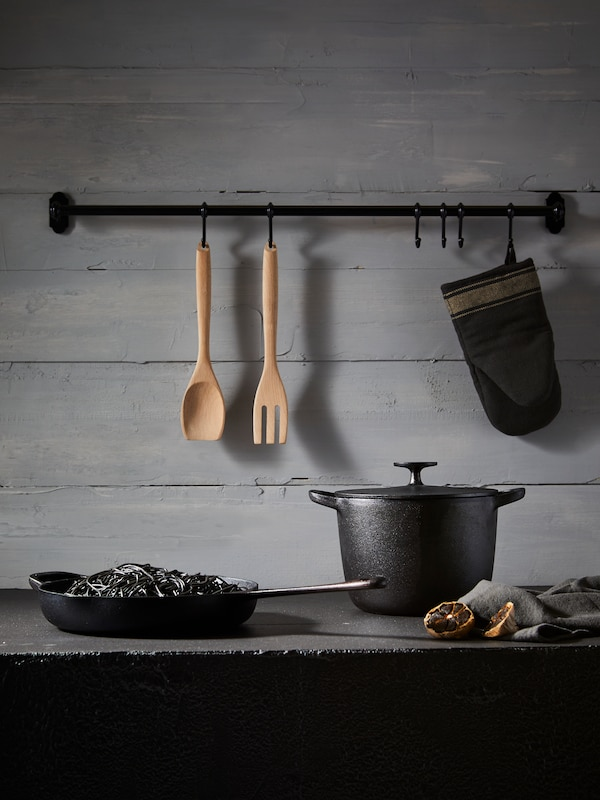 A black cast iron pot and pan on a counter, with wooden utensils hanging from a rack above.