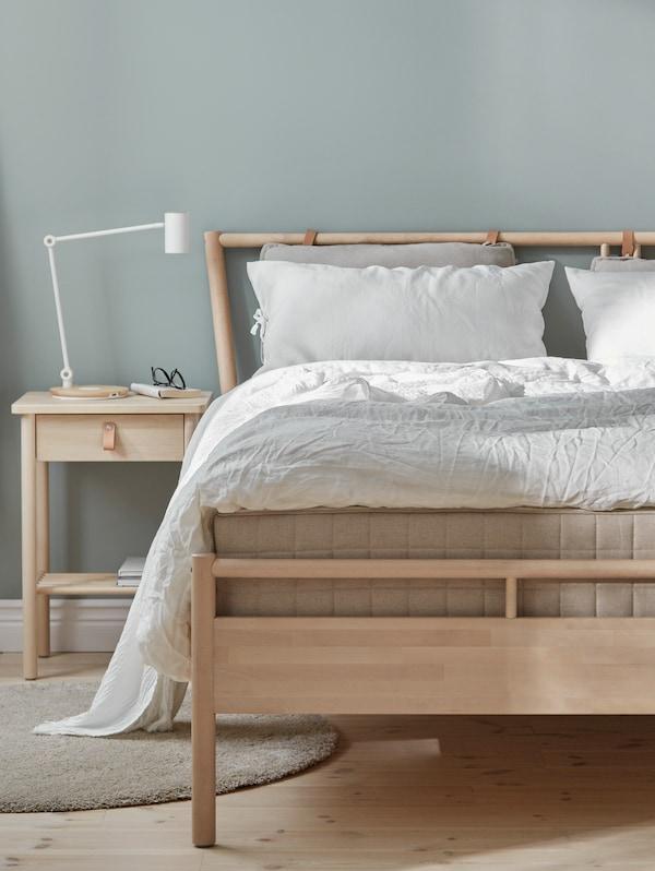 غرفة نوم بحوائط رماديبهاسرير بهيكل سرير BJÖRKSNÄS من خشب البتولا وطاولة سرير جانبية من خشب البتولا وبياضات سرير بيضاء.