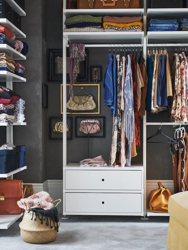 Kombinasi storan ELVARLI dengan dua laci dan para serta rel pakaian menyimpan pakaian berwarna terang.