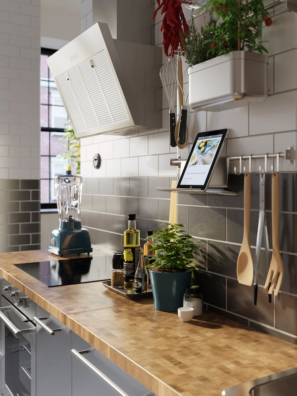 A kitchen counter with a rail on the wall above holding a tablet on a tablet stand. Cooking utensils hang from the rail.