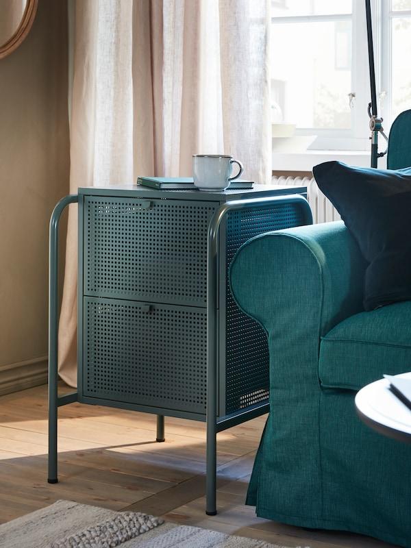 Una cómoda NIKKEBY gris verdoso con 2 cajones con una taza GLADELIG y un libro sobre ella, junto a un sofá de EKTORP turquesa oscuro.