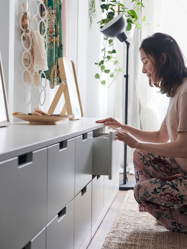 A woman opening a drawer from a white NORDLI chest of drawers with a wooden mirror and a nearby lamp.