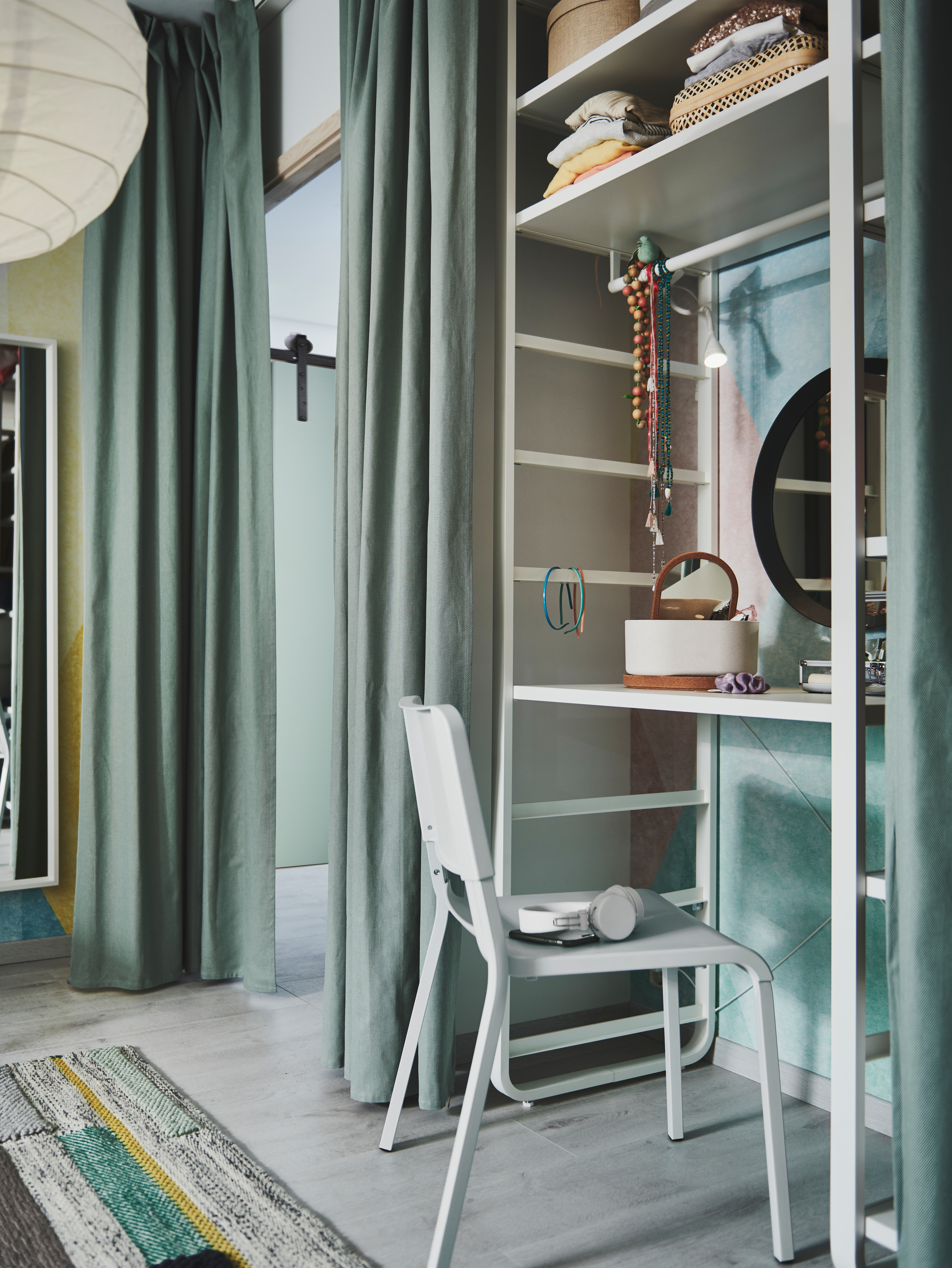 A green room with an ELVARLI shelf unit being used as dressing table with TIBAST curtains used as a door pulled to one side.