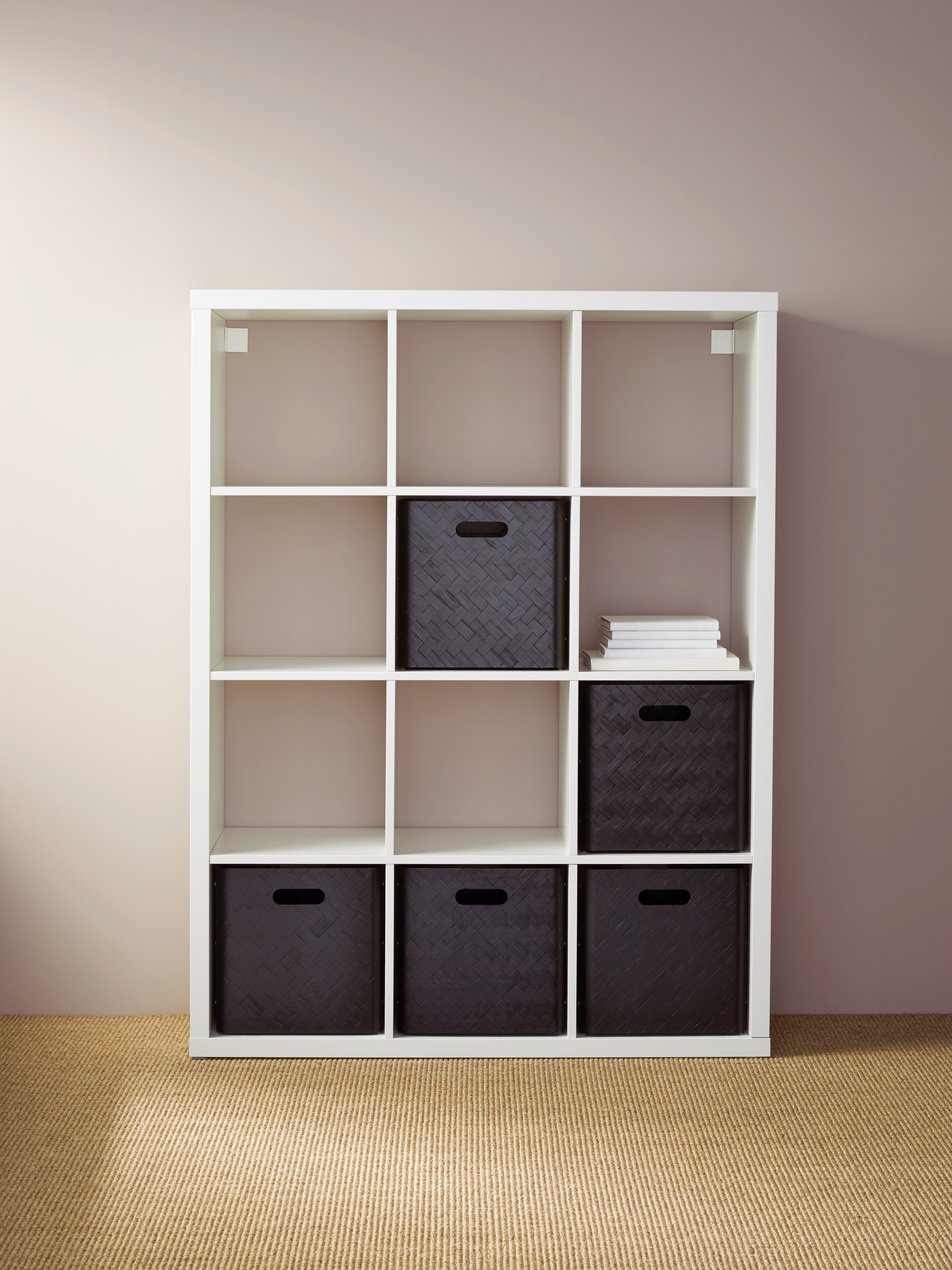 A white KALLAX shelving unit with twelve, box-like shelves is secured to a wall. It holds a stack of books and bamboo boxes.