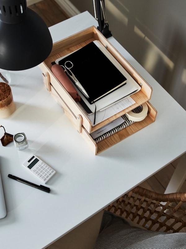 Tesoiras e papeis nunha bandexa para cartas KLÄMMEMACKA sobre unha mesa MELLTORP branca e unha lámpada de traballo TERTIAL pendurada gris escuro.