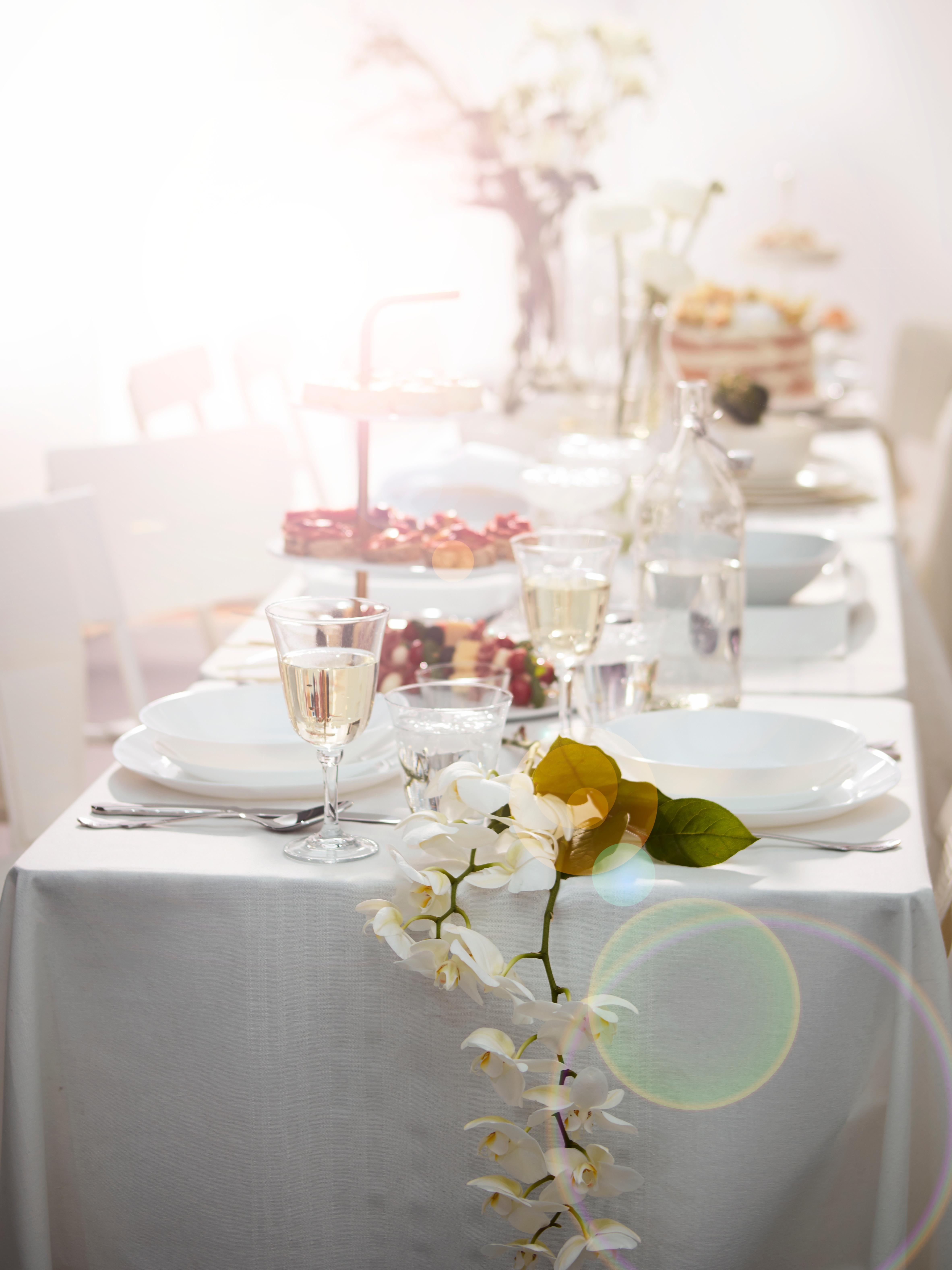 OFTAST bijeli tanjuri na stolu obasjanom suncem, pripremljeni za svečanu večeru sa stolnjakom i čašama za vino.