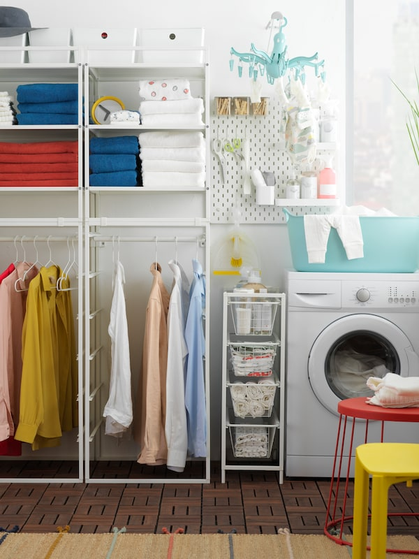 A laundry room with a washing machine, a clothes rack and a laundry basket.