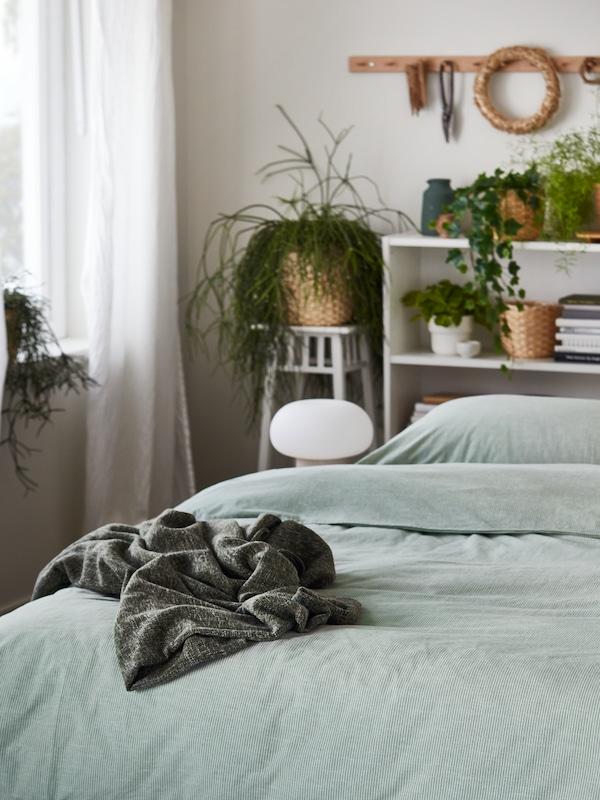 Krevet s BERGPALM posteljinom sa zelenim prugama. Bijele BILLY komode pored njegovog uzglavlja pune su zelenih biljaka.