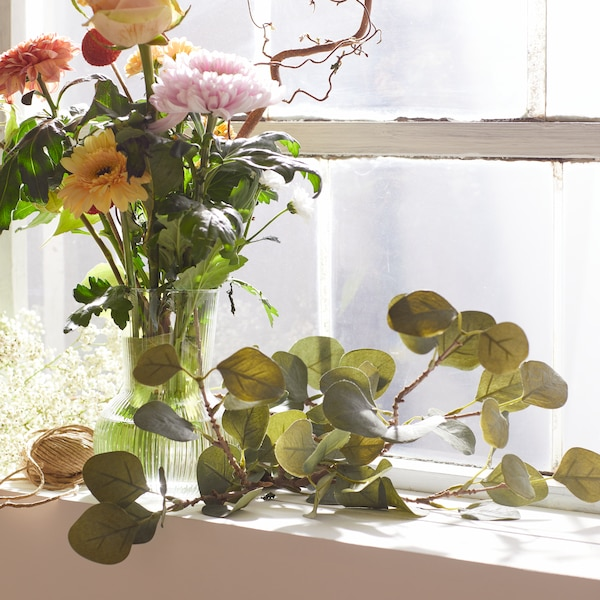 A bouquet of flowers on a windowsill, with more greenery.