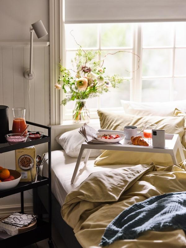 Černý vozík NISSAFORS se vším potřebným na snídani, vedle plného podnosu umístěného na posteli s ložním prádlem ÄNGSLILJA.