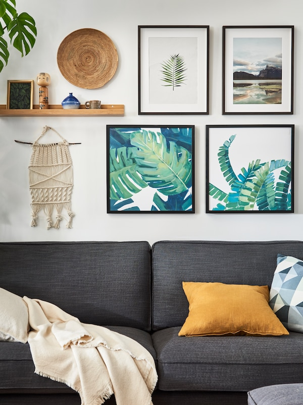 A KIVIK two-seat sofa in anthracite colour beneath an art wall made up of four framed pictures and various curios.