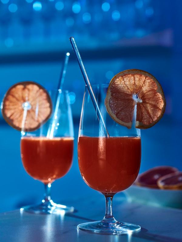 O cameră scăldată în lumină albastră. Două pahare de bere STORSINT cu picior, cu suc de portocale roșii și o felie de fruct pe marginea fiecăruia.