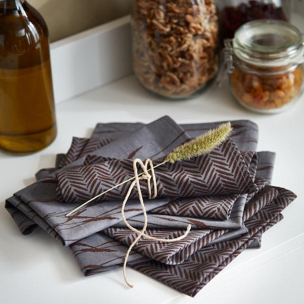 Una pila di tovaglioli grigi ripiegati HÖSTKVÄLL sta su una credenza. Un tovagliolo è legato con spago e decorato con un fiore essiccato.